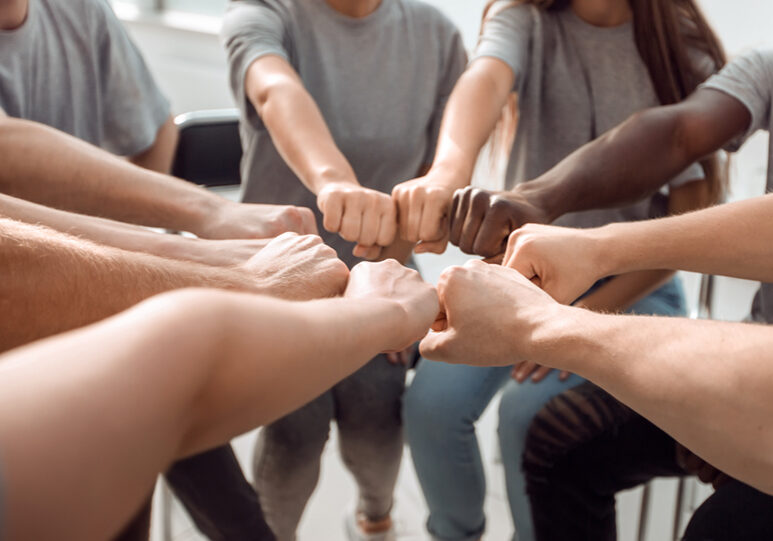close up. confident young team joining their hands. the concept of unity
